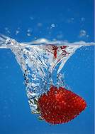 A strawberry plunging into sparkling water.