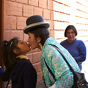 Cholita wrestler Yolanda La Amorosa greets her daughter Adriana as she picks her up from school in La Paz, Bolivia. Yolanda is part of the 'Titans of the Ring' wrestling group who perform every  Sunday at El Alto's Multifunctional Centre. Bolivia. The wrestling group includes the fighting Cholitas, a group of Indigenous Female Lucha Libra wrestlers who fight the men as well as each other for just a few dollars appearance money. El Alto, Bolivia, 17th March 2010. Photo Tim Clayton