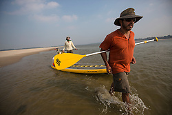 Martin Cavada and Jeremiah Kent portage their boards through a section of shallow water on the Ganga.
