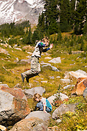 Boy jumping off rock over a girl in a mountain valley