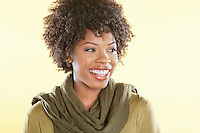 Happy African American woman with a stole round her neck looking away over colored background