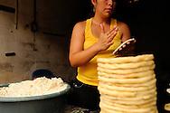 Woman preparing tortillas in a street market.Suchitoto, El Salvador