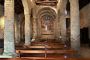 General view of the nave with cylindrical columns separating from the aisles, Sant Climent de Taull church, 1123, consecrated by Ramon Guillem, the bishop of Roda, Taull, Province of Lleida, Catalonia, Spain. The cylindrical columns separating the nave from its aisles have no capitals. The murals were removed to the MNAC (National Art Museum of Catalonia, Barcelona) in 1922, to prevent the theft. They are frescos and were removed by painting them with horsehide glue and then peeling off the hardened glue, carrying the pigments of the mural with it. Among the murals is a striking rendition of Christ Pantocrator in the central apse. Sant Climent de Taull is part of the Catalan Romanesque churches of the Vall de Boí which were declared a World Heritage Site by UNESCO in November 2000. Picture by Manuel Cohen