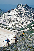 "Hikers ascend snowfields on Tsouka Rossa Pass on the Tymfi Massif, north Pindus Mountains (Pindos or Pindhos), Zagoria, Epirus/Epiros, Greece, Europe. Mount Tymfi (or Greek: , also transliterated Timfi, Tymphe, or Tymphi) forms a massif with its highest peak, Gamila, at 2497 meters (8192 feet), the sixth highest in Greece. Zagori (Greek: ) is a region and a municipality in northwestern Greece containing 45 villages collectively known as Zagoria (Zagorochoria or Zagorohoria). Published in ""Pindos: The National Park"" (2010) by Alexander G. Tziolas, preface by Tom Dempsey et al, ISBN 978-960-98795-3-8."
