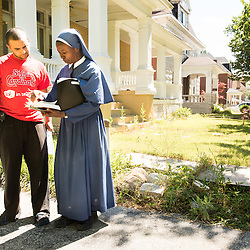 Teak Phillips | St. Louis Review | @TeakPhillips<br /> <br /> Sister Mary Paschal of the Society of the Mother of Peace went door-to-door in St. Augustine Parish in north St. Louis to proclaim the Gospel message. She met and prayed with Chris Madison, who lives in the 5300 block of Maple Avenue in the Visitation Park neighborhood.