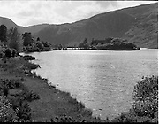 06/1954<br /> June1954<br /> Gougane Barra and St Finbarr's Monastery, Co. Cork.<br /> Gougane Barra is a settlement, west of Macroom in County Cork, Ireland..The name Gougane Barra comes from Saint Finbarr, who is said to have built a monastery on an island in the lake nearby during the 6th century. The present ruins date from around 1700 when a priest called Denis O'Mahony retreated to the island. During the times of the Penal Laws, Gougane Barra's remoteness meant that it became a popular place for the celebration of the Roman Catholic Mass..Afforestation of the area around the settlement began in 1938 and Gougane Barra is now home to a 1.42 square kilometre forest park which is home to a number of mammal and bird species.