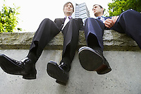 Two business men sitting side by side on wall low angle view