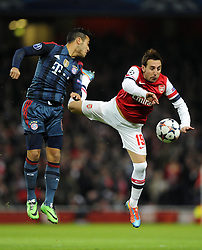 Bayern Munich's Thiago Alcantara battles for the high ball with Arsenal's Santi Cazorla - Photo mandatory by-line: Joe Meredith/JMP - Tel: Mobile: 07966 386802 19/02/2014 - SPORT - FOOTBALL - London - Emirates Stadium - Arsenal v Bayern Munich - Champions League - Last 16 - First Leg