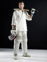 Cricket player standing holding bat on shoulder