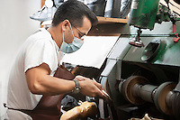 Side view of skilled cobbler rubbing shoe sole in machinery