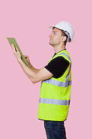 Side view of a male construction worker with clipboard looking away over pink background