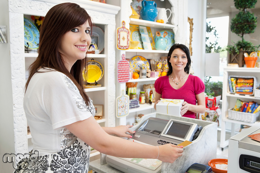 Portrait of a young caterer at checkout counter with female customer in background
