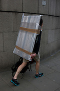 A man walks through the City of London carrying a bubble-wrapped flatscreen TV on his back.