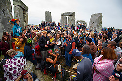 © Licensed to London News Pictures. 21/06/2015. Salisbury, UK. Revellers take part in celebrations to mark the summer solstice at Stonehenge prehistoric monument on June 21, 2015 in Wiltshire, England. Thousands of revellers gather at the 5,000 year old stone circle in Wiltshire to see the sunrise on the Summer Solstice dawn. The solstice sunrise marks the longest day of the year in the Northern Hemisphere. Photo credit: Tolga Akmen/LNP