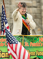 Goshen, New York - Grand Marshall Sister Ann Daly  waves to marchers from the reviewing stand on Main Street during the 40th annual Mid-Hudson St. Patrick's Parade  on March 13, 2016.
