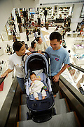 Opening weekend of Siam Paragon shopping center. Paragon Department Store. Young couple with baby.