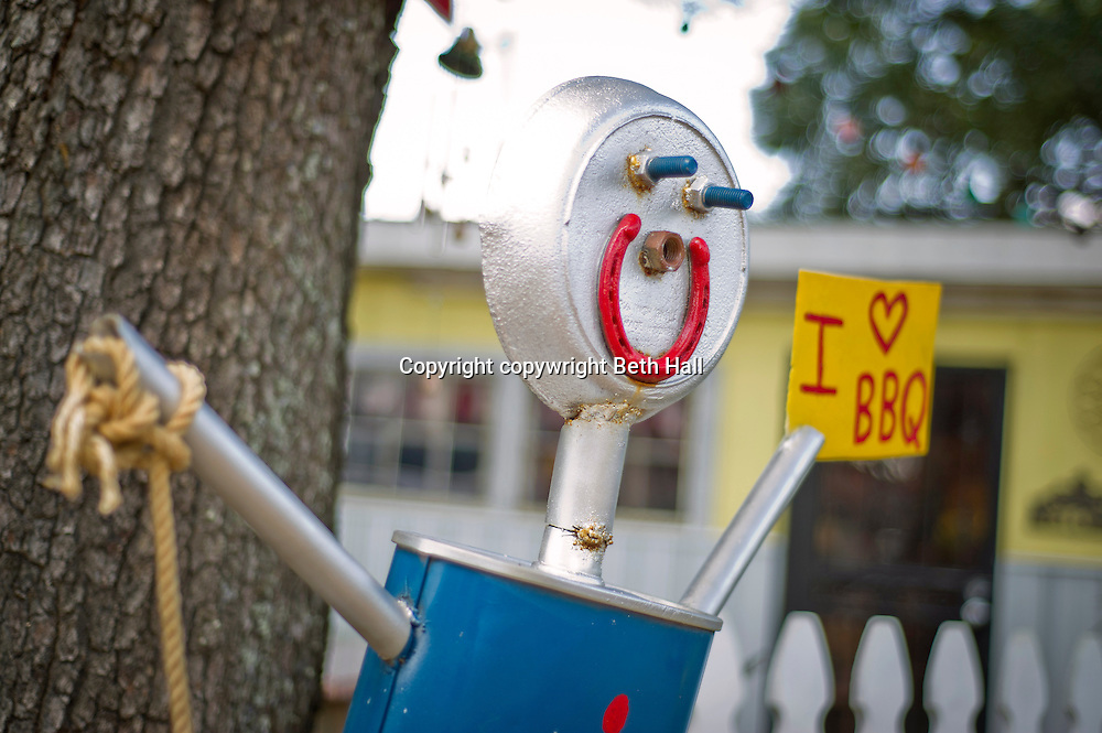 A sculpture made of scrap metal parts holds a sign that says I love BBQ.