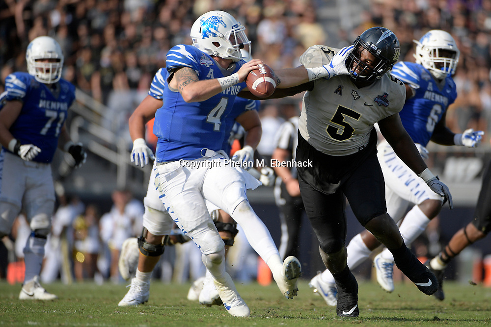 Memphis quarterback Riley Ferguson (4) eludes Central Florida defensive lineman Jamiyus Pittman (5) during the second half of the American Athletic Conference championship NCAA college football game Saturday, Dec. 2, 2017, in Orlando, Fla. Central Florida won 62-55. (Photo by Phelan M. Ebenhack)