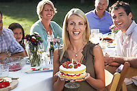 Family at dining table outdoors woman holding strawberry cake