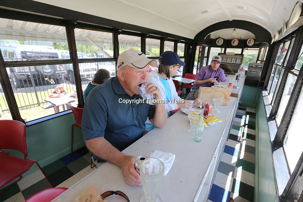 Tim West, left, and his wife, Wanda, get to sit at the counter and enjoy their burger during Saturday's Dudie Burger Festival at the Oren Dunn Musuem.