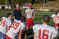 Coach Jim Fitzgerald and Coach Craig Kozens talks to the Laconia Sachem football team during Thursday afternoon's practice.  (Karen Bobotas/for the Laconia Daily Sun)