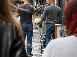"Compton Street, Soho, London, June 13th 2016. A pair of white roses, a solemn memorial to the 50 people killed at gay club Pulse in Orlando on 12 June, is attached to the balustrade outside The Admiral Duncan, a LGBT-friendly bar that knows too well the price of homophobia, bombed by Neo-Nazi David Copeland on 30 April 1999, killing three people and wounding 70. The message on the card reads, ""Compton Street, Soho, London, June 13th 2016. A pair of white roses, a solemn memorial to the 50 people killed at gay club Pulse in Orlando on 12 June, is attached to the balustrade outside The Admiral Duncan, a LGBT-friendly bar that knows too well the price of homophobia, bombed by Neo-Nazi David Copeland on 30 April 1999, killing three people and wounding 70. The message on the card reads, ""To Orlando, LOVE IS LOVE! Soho stands with you."" and is signed ""James and Talia"". PICTURED: Two men walk hand in had along Old Compton Street."