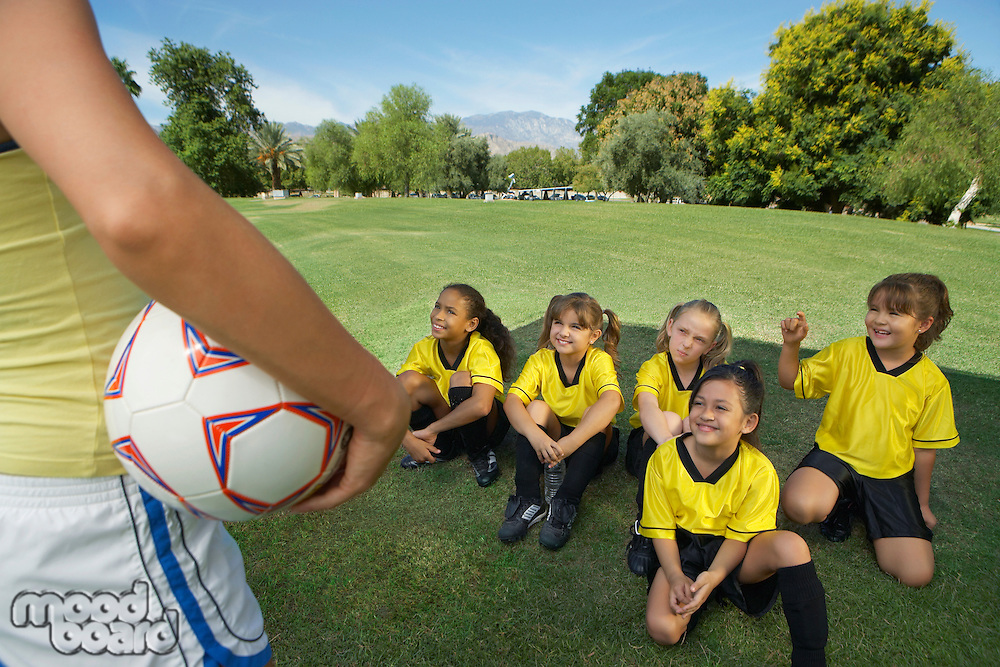 Coach standing in front of group of girl soccer players (7-9 years) sitting on lawn, elevated view