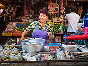 "12 JUNE 2015 - BANGKOK, THAILAND: A congee vendor in Khlong Toey Market in Bangkok. Congee is rice porridge popular in Southeast Asia. Khlong Toey (also called Khlong Toei) Market is one of the largest ""wet markets"" in Thailand. The market is located in the midst of one of Bangkok's largest slum areas and close to the city's original deep water port. Thousands of people live in the neighboring slum area. Thousands more shop in the sprawling market for fresh fruits and vegetables as well meat, fish and poultry.          PHOTO BY JACK KURTZ"
