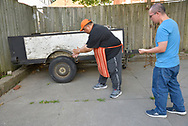CANADA, Windsor. 21 September 2018. Two men drop sacred tobacco on the site where a man died from a drug overdose. Steve Mull leads a traditional ceremony near the site of an overdose victim behind Street Health. About twenty people and two media attend the dignified Indigenous smudging ceremony. In respect of the tradition the deceased is not named.