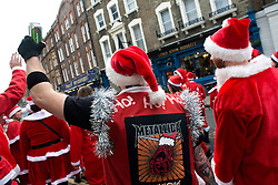 © Licensed to London News Pictures./14/2013. London, UK. Participants dressed in Father Christmas costumes gather for the annual Santacon celebration on Marchmont Street.Photo credit : Peter Kollanyi/LNP