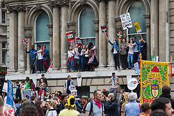 London, June 20th 2015. Thousands of people converge on the streets of London to join the People's Assembly Against Austerity's march from the Bank of England to Parliament Square. PICTURED: Protesters dance on the windowsil of a building in Whitehall.