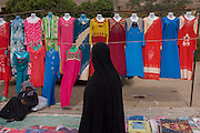 A local woman walks past colourful dress designs on a stall at the weekly market at Qurna, a village on the West Bank of Luxor, Nile Valley, Egypt.