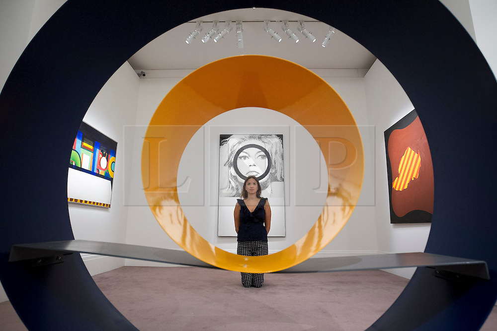 "© Licensed to London News Pictures. 03/09/2013. London, UK. A Sotheby's employee is seen through David Annesley's ""Untitled (Circle)"" (1966) with Gerald Laing's ""Bridget Bardot"" (1963) in the background during the press view for an exhibition of art from the 1960's at Sotheby's in London today (03/09/2013). The exhibition, entitled ""The New Situation: Art in London in the Sixties"" and located at the auction house's New Bond Street building, is open to the public from 4th to the 11th of September 2013. Photo credit: Matt Cetti-Roberts/LNP"