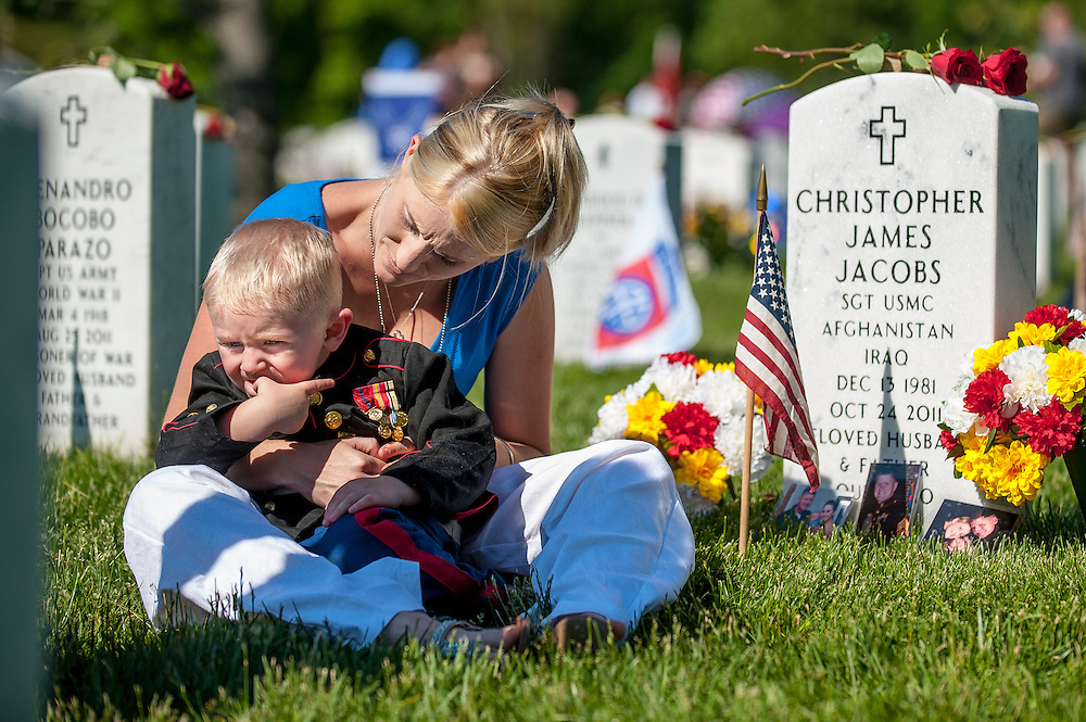 On Memorial Day, Brittany Jacobs of Hertford, North Carolina sits with her son, Christian, 3, at the gravesite of her husband, Marine Sgt. Christopher Jacobs at Arlington National Cemetery in Arlington, Virginia, USA, on 26 May 2014.