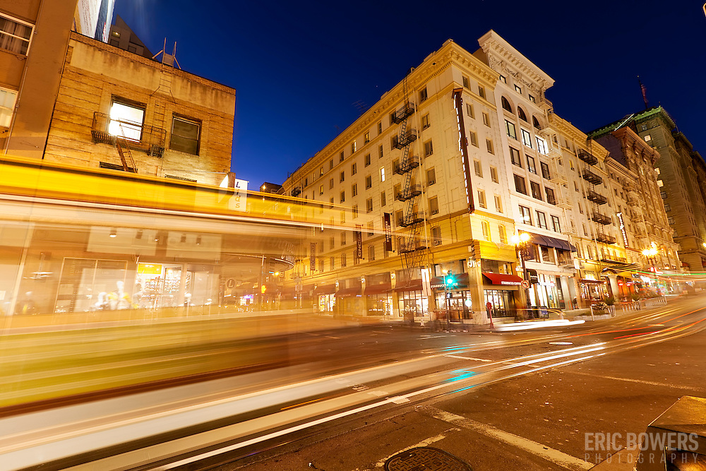Intersection of Powell and Ellis Streets in Union Square area of downtown San Francisco, CA. Streetcar traffic motion blur at dusk.