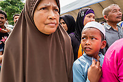 07 JULY 2013 - NARATHIWAT, NARATHIWAT, THAILAND:  Thai Muslims in Narathiwat wait in line to get rice and snacks from Royal Thai Marines during a civil affairs program in Narathiwat. Royal Thai Marines in Narathiwat province held a special ceremony Sunday in advance of Ramadan. They presented widows, orphans and indigent people with extra rice and food as a part of the Thai government's outreach to resolve the Muslim insurgency that has wracked southern Thailand since 2004. The Holy Month of Ramadan starts on about July 9 this year. Muslims are expected to fast from dawn to dusk, engage in extra prayers, recitation of the Quran and perform extra acts of charity during Ramadan. It is the holiest month of the year for Muslims.   PHOTO BY JACK KURTZ
