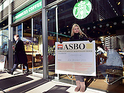 © Licensed to London News Pictures. 04/12/2012. London, UK Lauren Tinney from the GMB union holds a placard outside a Stabucks Coffee Shop at the headquarters, awarding Starbucks an 'ASBO for antisocial behaviour' after being prevented from handing it in to the headquarters reception. GMB union members demonstrate outside Starbucks Head Quarters on Chiswick High Road, London, over complaints that the coffee firm does not pay its staff the Living Wage, today 4th December 2012. Photo credit : Stephen Simpson/LNP