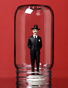 business doll under a glass jar against a red background