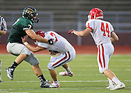 Washington's Reid Snitker (3) is sacked by Kennedy's Drew Heitland as Washington's Connor Vincent (44) looks on during their game at Kinston Stadium in Cedar Rapids on Friday, August 30, 2013.