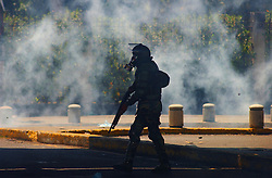 A Member of the National Guard walks through a cloud of  tear gas towards anti-government demonstrators after an  opposition march  to demand that President Chavez  submit to a recall referendum turned violent.  The march was held on the first day of the G15 summit in Caracas.