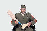 Portrait of US military officer in wheelchair holding prosthesis foot over gray background