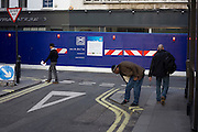 Pedestrians walk over road junction near Crossrail construction site.
