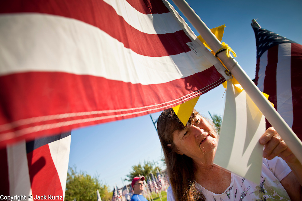 """10 SEPTEMBER 2011 - TEMPE, AZ:     JACQUELYN POWER, from Tempe, AZ, looks at the flags in the """"Healing Field"""" in Tempe, Saturday. The """"Healing Field,"""" a display of 2,996 flags, one for each person killed in the September 11 terrorists attacks on the World Trade Center in New York City and Washington DC, have become an annual tradition in Tempe, AZ. The event is sponsored by the National Exchange Club.    PHOTO BY JACK KURTZ"""