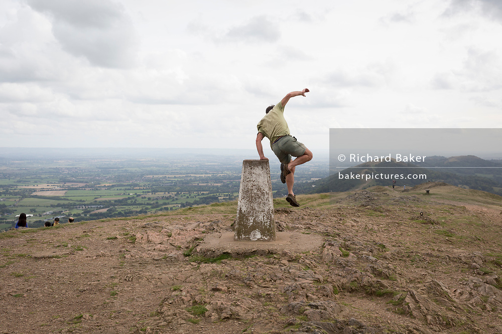 A hill climber jumps down off the trig-point on the top of The Beacon, on 15th September 2018, in Malvern, Worcestershire, England UK. Worcestershire Beacon, also popularly known as Worcester Beacon, or locally simply as The Beacon, is a hill whose summit at 425 metres (1,394 ft)[1] is the highest point of the range of Malvern Hills that runs about 13 kilometres (8.1 mi) north-south along the Herefordshire-Worcestershire border, although Worcestershire Beacon itself lies entirely within Worcestershire. A triangulation station, also known as a triangulation pillar, trigonometrical station, trigonometrical point, trig station, trig beacon, or trig point, and sometimes informally as a trig, is a fixed surveying station, used in geodetic surveying and other surveying projects in its vicinity.