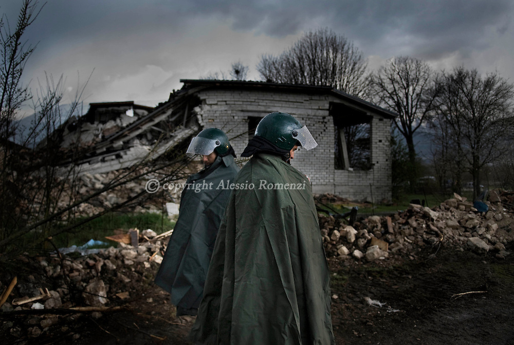 .Two soldiers stand in front of a house collapsed on April 6, 2009 during a eartquake in Onna, a small town some 10 kilometers from L'Aquila, epicentre of an earthquake which jolted central Italy early morning. A violent earthquake jolted central Italy killing at least 92 people and injuring 1,500 as buildings and homes in the walled medieval town of L'Aquila were reduced to rubble.© ALESSIO ROMENZI