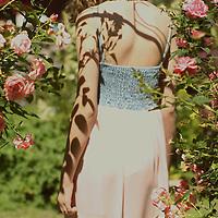 Female youth wearing a long summer dress walking between rose bushes in a garden
