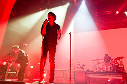© Licensed to London News Pictures. 12/02/2014. London, UK.   Phoenix performing live at Brixton Academy.   In this picture - Laurent Brancowitz (left), Thomas Mars (centre), Thomas Hedlund (right).  Phoenix is a french alternative rock band comprising of members Thomas Mars (vocals), Deck D'Arcy (Bass,Keyboards), Laurent Brancowitz (guitar, keyboards), Christian Mazzalai (guitar).  Photo credit : Richard Isaac/LNP