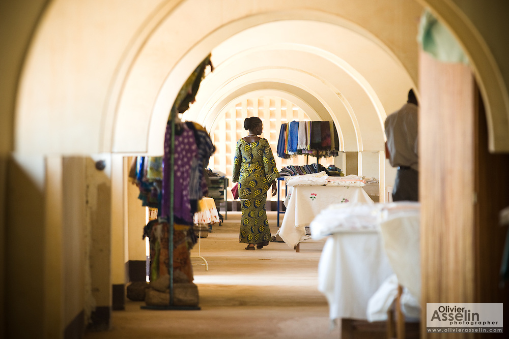 A woman walks past stores at the Village Artisanal de Ouagadougou, a cooperative that employs dozens of artisans who work in different mediums, in Ouagadougou, Burkina Faso, on Monday November 3, 2008.
