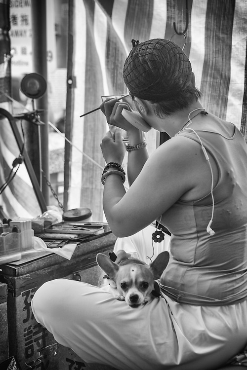 A chihuahua rests on an actresses lap as she prepares her makeup.