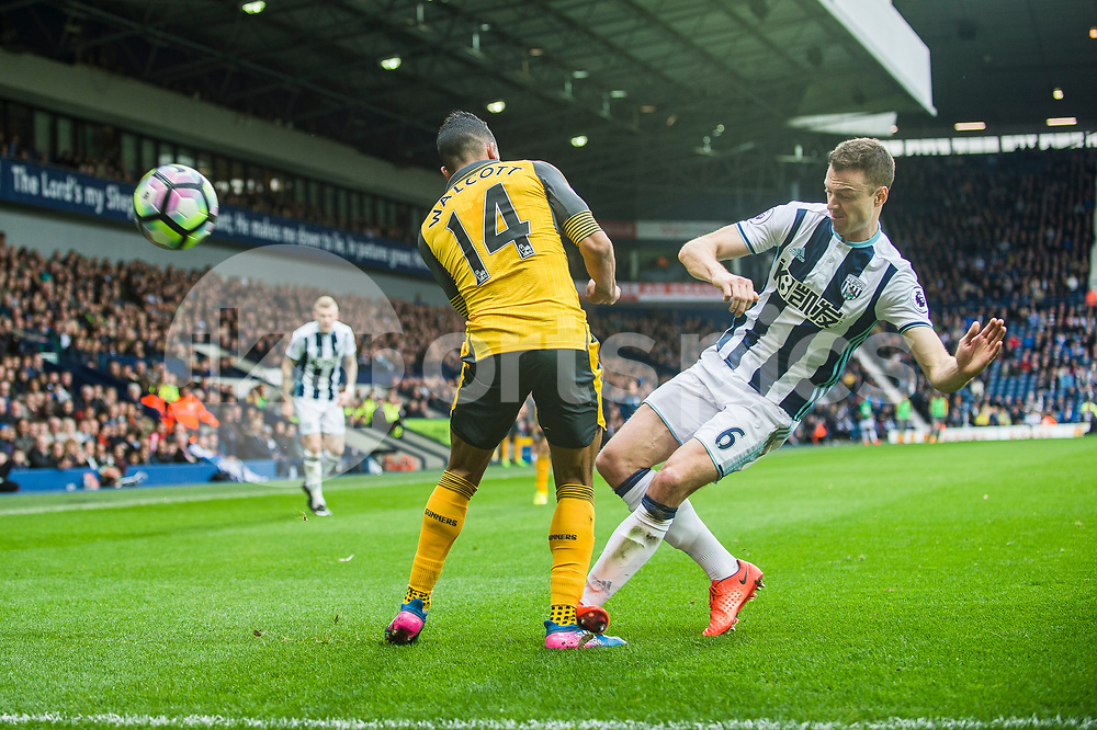 Jonny Evans of West Bromwich Albion tackles Theo Walcott of Arsenal during the Premier League match between West Bromwich Albion and Arsenal at The Hawthorns, West Bromwich, England on 18 March 2017. Photo by Darren Musgrove.